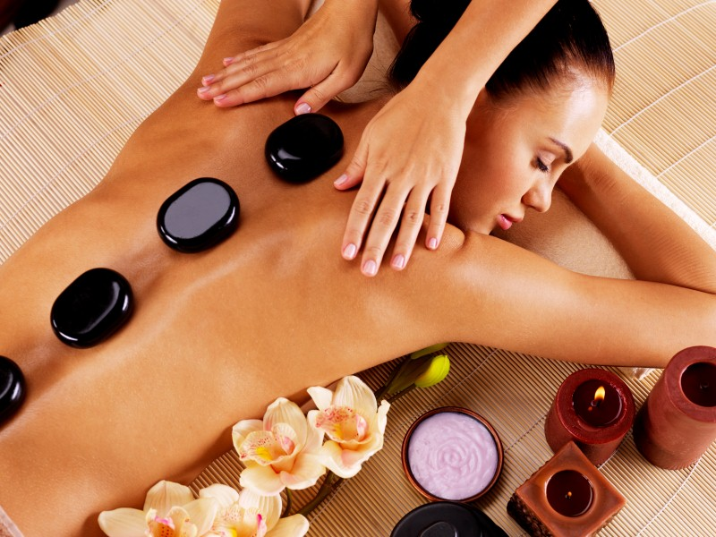 Adult woman having hot stone massage in refined beauty day spa
